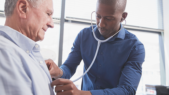 Male doctor using a stethoscope to check the chest of a patient